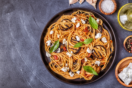 Pasta alla Norma - traditional Italian food with eggplant, tomato, cheese and basil, top view.