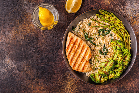Pollo alla griglia con riso integrale, spinaci, broccoli, asparagi, concetto di dieta, mangiare sano.