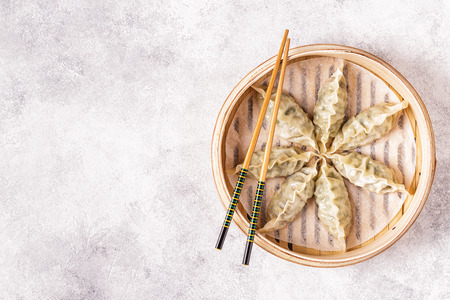 Asian dumplings, soy sauce, chopsticks. Top view, copy space.