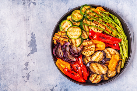 Gegrilltes Gemüse auf einem Teller mit Sauce, Draufsicht.