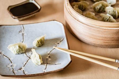 Asian gyoza, dumplings snack, chopsticks, steamer, selective focus.