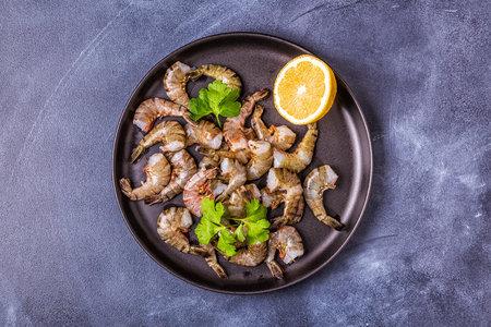 Raw shrimps with parsley and lemon, top view.