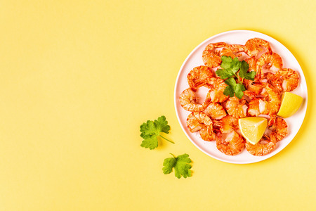 Grilled shrimps with lemon parsley and garlic on pastel background. Stock Photo