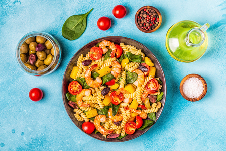 Fusili pasta salad with shrimps, tomatoes, peppers, spinach, olives, top view.