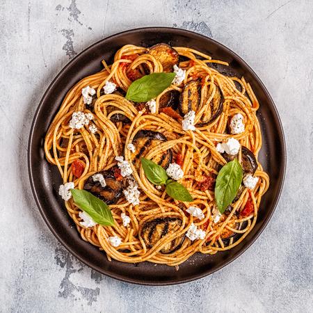 Pasta alla Norma - cuisine italienne traditionnelle avec aubergine, tomate, fromage et basilic, vue du dessus. Banque d'images