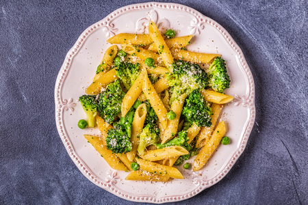 Pasta with broccoli, green peas, garlic, cheese, top view.