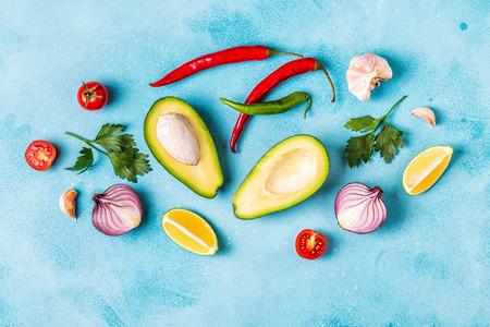 Ingredientes para guacamole: aguacate, lima, tomate, cebolla y especias, vista superior.