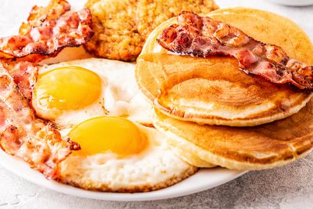 Desayuno americano completo saludable con huevos, tocino, panqueques y latkes, enfoque selectivo.