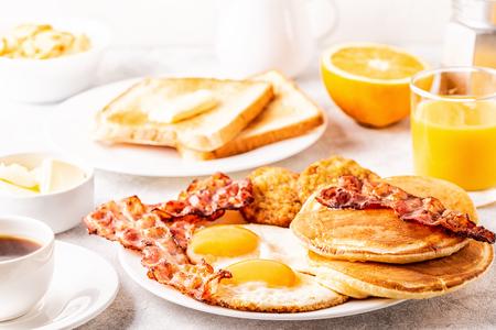 Prima colazione americana completa sana con i pancake ed i Latkes della pancetta affumicata delle uova, fuoco selettivo. Archivio Fotografico