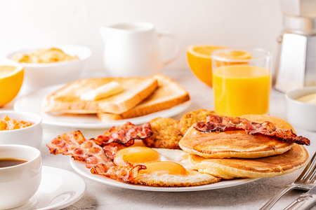 Healthy Full American Breakfast with Eggs Bacon Pancakes and Latkes, selective focus. Stock Photo