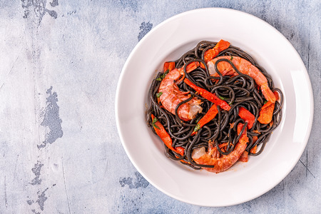 Black spaghetti with prawns and vegetables, top view. Archivio Fotografico - 114838343