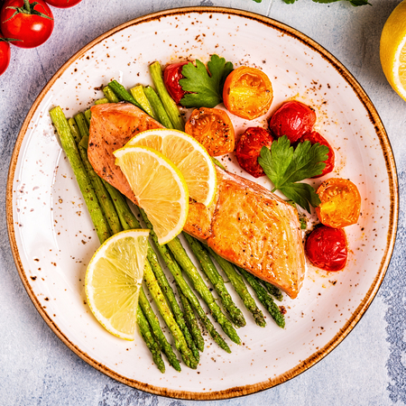 Grilled salmon with asparagus and tomatoes, top view.