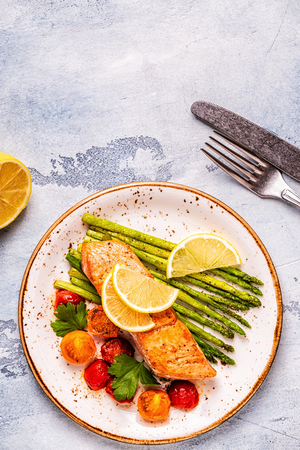 Grilled salmon with asparagus and tomatoes, top view. Фото со стока - 115481014