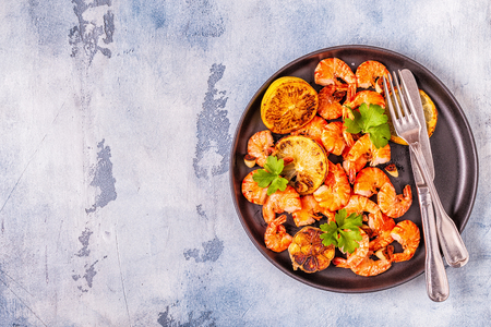 Grilled shrimps with lemon parsley and garlic, top view.