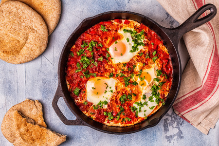 Shakshuka in a Frying Pan. Eggs Poached in Spicy Tomato Pepper Sauce. Stockfoto