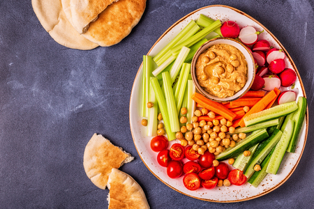 Hummus with various fresh raw vegetables, top view. Stockfoto