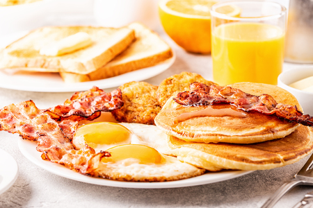 Healthy Full American Breakfast with Eggs Bacon Pancakes and Latkes, selective focus.
