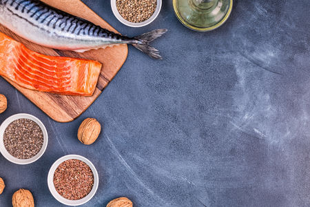Sources of omega 3 - mackerel, salmon, flax seeds, hemp seeds, chia, walnuts, flaxseed oil. Healthy eating concept. Top view with copy space. 免版税图像 - 117814115