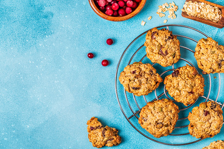 Homemade oatmeal cookies with cranberries and pumpkin seeds, top view.