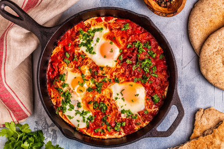 Shakshuka in a Frying Pan. Eggs Poached in Spicy Tomato Pepper Sauce. 免版税图像