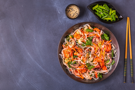 Asian salad with rice noodles, shrimp and vegetables, top view.