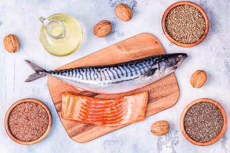 Sources of omega 3 - mackerel, salmon, flax seeds, hemp seeds, chia, walnuts, flaxseed oil. Healthy eating concept. Top view with copy space. Banco de Imagens