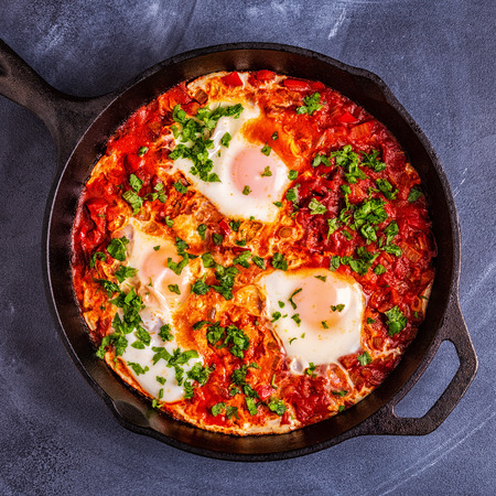 Shakshuka in a Frying Pan. Eggs Poached in Spicy Tomato Pepper Sauce. Stock Photo