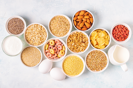Ingredients for healthy breakfast - cereals, grains, dairy products, seeds, nuts.