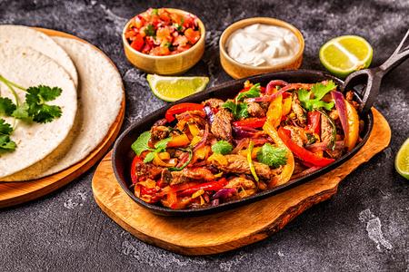 FAJITAS con pimiento y cebolla de colores, acompañadas de tortillas, salsa y crema agria.