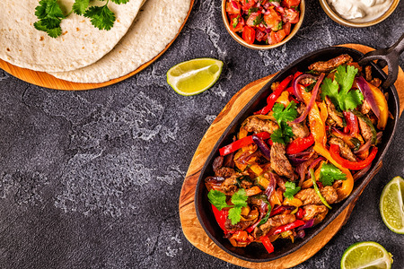 FAJITAS with colored pepper and onions, served with tortillas, salsa and sour cream.