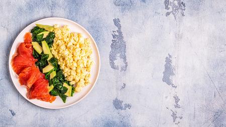 Ketogenic diet breakfast, scrambled eggs, salmon, avocado, spinach, top view.