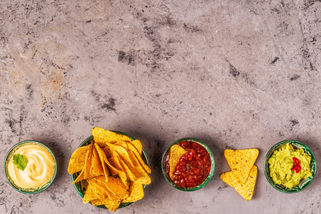 Mexican food background: guacamole, salsa, cheesy sauces with nachos, top view. Imagens