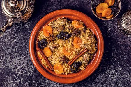 Traditionele Marokkaanse tajine van kip met gedroogde vruchten en kruiden, bovenaanzicht.