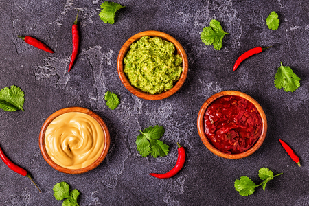 Mexican food background: guacamole, salsa, cheesy sauces with ingredients on black background, top view.