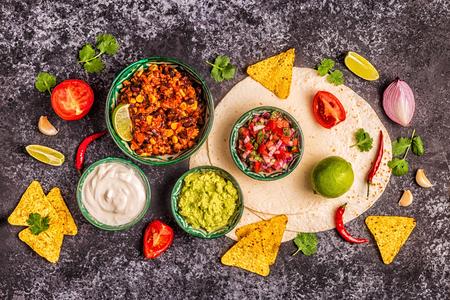 Mexican food concept: tortillas, nachos with guacamole, salsa, chili con carne, top view. Zdjęcie Seryjne