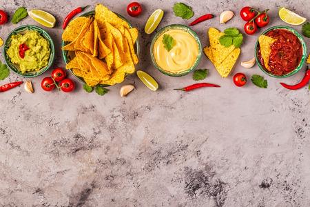 Contexte de la cuisine mexicaine : guacamole, salsa, sauces au fromage avec nachos, vue de dessus.