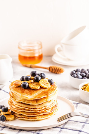 Pancakes with banana,  blueberries on white plate, selective focus.