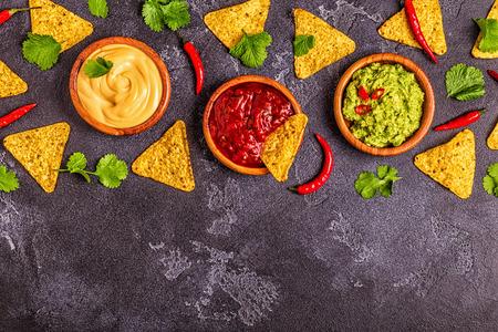 Fondo de comida mexicana: guacamole, salsa, salsas de queso con ingredientes sobre fondo negro, vista superior.