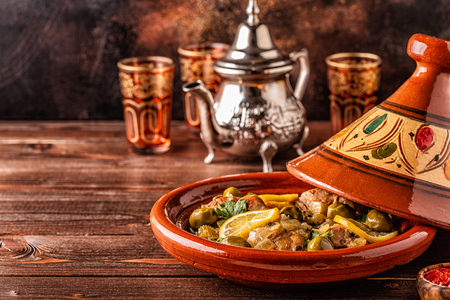 Traditional Moroccan chicken tagine with olives and salted lemons, selective focus.