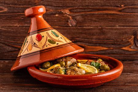 Traditionelle marokkanische Hühnchen-Tajine mit Oliven und gesalzenen Zitronen, selektiver Fokus.