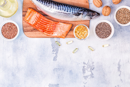 Sources of omega 3 - mackerel, salmon, flax seeds, hemp seeds, chia, walnuts, flaxseed oil. Healthy eating concept. Top view with copy space. Imagens - 121667826