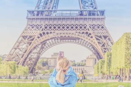 Girl tourist taking pictures of Eiffel Tower.