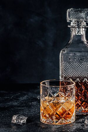 Glass of the whiskey with a square decanter on a black stone background. Zdjęcie Seryjne