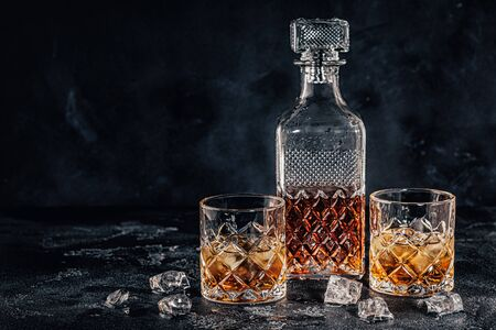 Glasses of the whiskey with a square decanter on a black stone background. 版權商用圖片