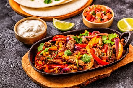 FAJITAS with colored pepper and onions, served with tortillas, salsa and sour cream. Stock Photo