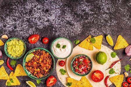 Mexican food concept: tortillas, nachos with guacamole, salsa, chili con carne, top view. Stock Photo