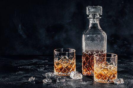 Gläser des Whiskys mit einem quadratischen Dekanter auf einem schwarzen Steinhintergrund.
