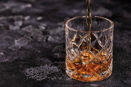 Whiskey on a stone dark background.