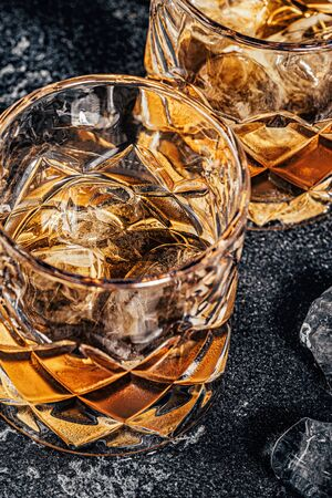 Whiskey with ice on a stone dark background.