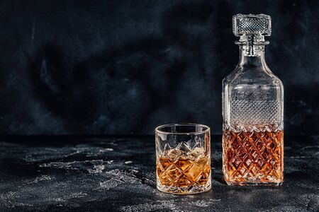 Glass of the whiskey with a square decanter on a black stone background. Stock fotó